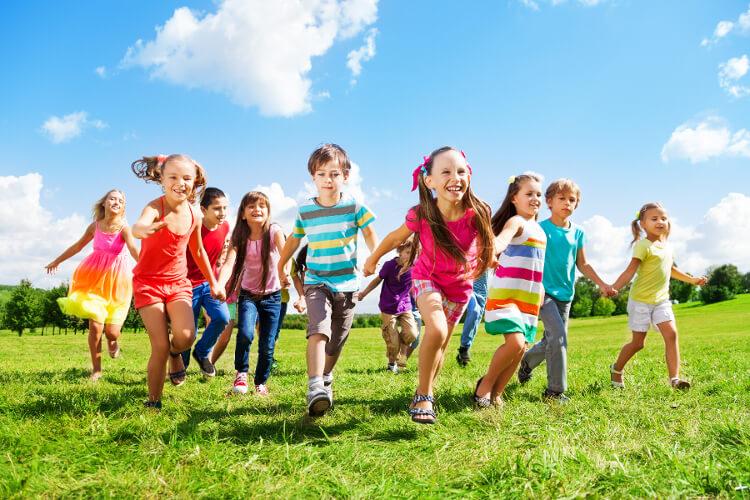 Kinder rennen Hand in Hand durch die Wiese