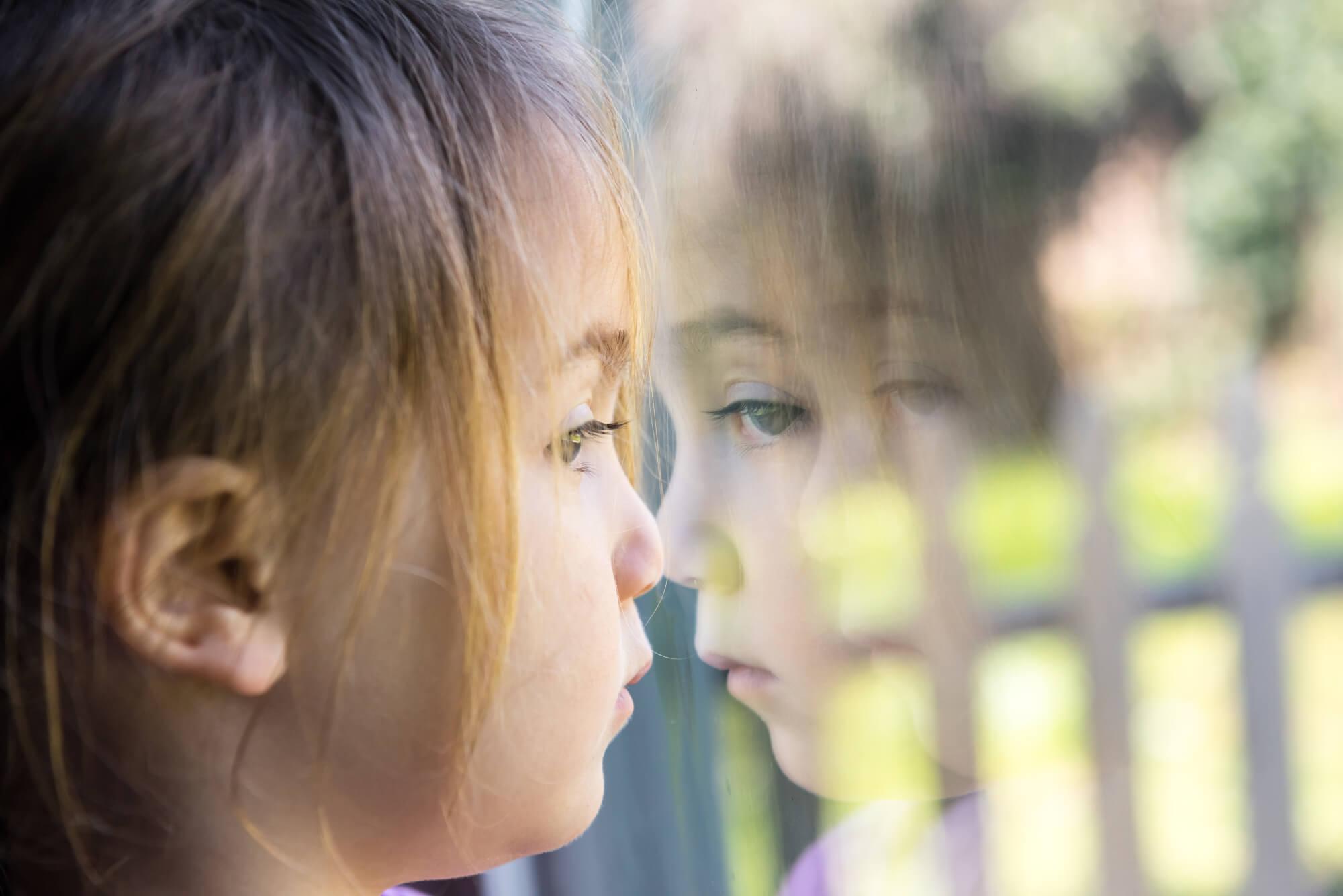 Trauriges Kind steht am Fenster
