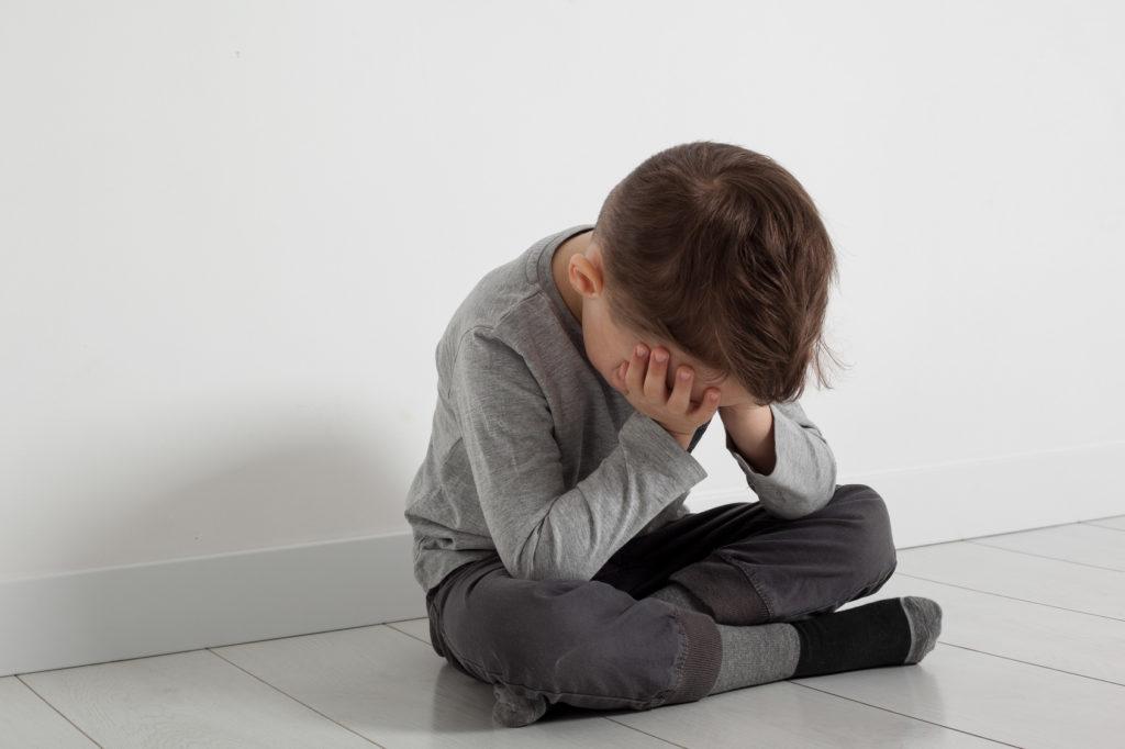 Kind sitzt deprimiert auf dem Boden