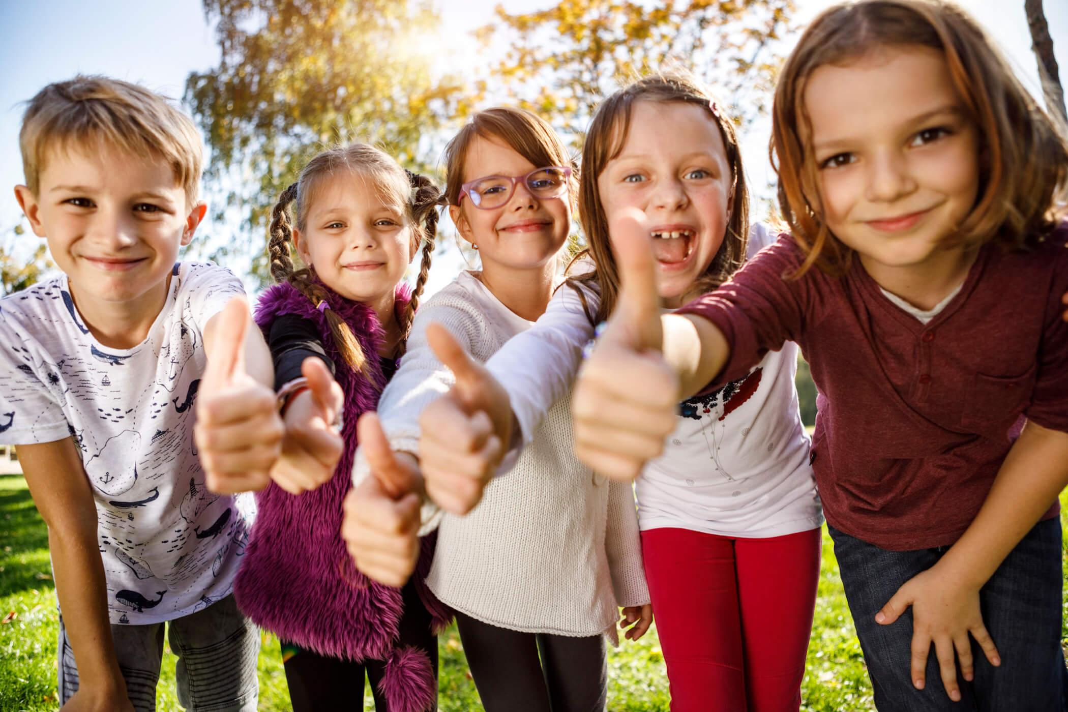 Fröhliche Kinder zeigen Daumen nach oben
